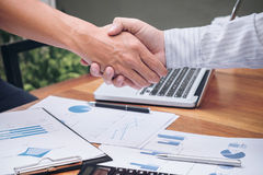 Close-up of two business people shaking hands while sitting at t Royalty Free Stock Images