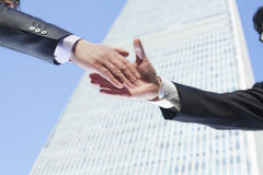 Close-up of two business people shaking hands by the World Trade Center in Beijing, China Royalty Free Stock Photos