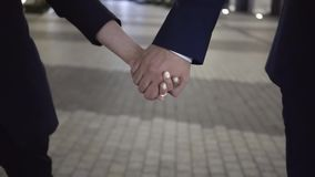 Young couple of business people walking in a night city holding hands, close up. Close up of two business people walking in a night city holding hands. Concept stock video footage