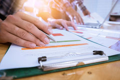 Close-up of two businessman hands pointing at turnover graph whi Stock Image