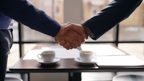 Close up of two businessman shaking hands in cafe after negotiations. Concept of: businessman working, business people, cafe interior, working together stock video