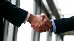 Close up of two businessman shaking hands. In office stock footage