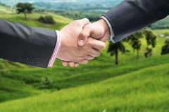 Close up of two businessmen shaking hands on the farmland. Stock Photo