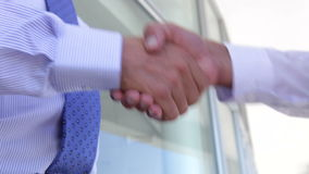 Close Up Of Two Businessmen Shaking Hands. Outside office building.Shot on Canon 5D MkII at 25fps stock footage