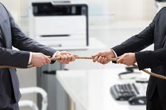 Two Businesspeople Playing Tug Of War stock photography