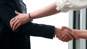 Close up of two businesswoman shaking hands. In office stock footage