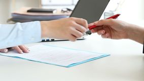 Businesswomen handshaking closing a deal. Close up of two businesswomen hands handshaking after closing a deal and signing contract in a desk with an office stock video footage
