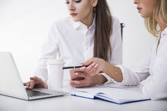 Close up of two businesswomen at a table in office. One is typing. The second is pointing with her pen. Royalty Free Stock Photos