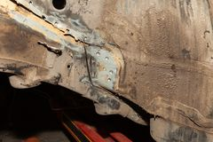 Close-up of two car body parts connected by spot welding after an accident. In a vehicle repair shop stock photos