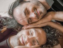 Close up of two Caucasian cheerful men pretend sleeping on the c. Close up of two Caucasian men pretend sleeping on the couch Royalty Free Stock Photography