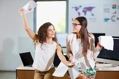 Two cheerful beautiful young business girls in the office. Close-up of two cheerful young business girls in white blouses holding documents Royalty Free Stock Photography
