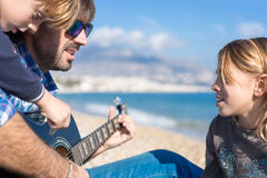 Close-up of two children and father singing song on beach Stock Photo