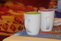 Tea for two. Close-up of two color bi tea cups, on a table with yellow, blue and embroidered tablecloth Stock Images