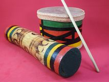 Close-up of two handmade Brazilian percussion instruments: small drum with drumstick and `ganzá`, a type of rattle. royalty free stock photo