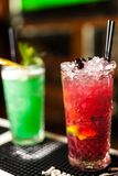 Close-up of two colorful red and green cocktails with lime and brown sugar in bar, blurred background. Colorful cocktails Stock Photo