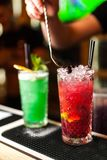 Close-up of two colorful red and green cocktails with lime and brown sugar in bar, blurred background. Colorful cocktails Stock Image