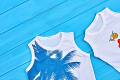 Close up of two cotton childrens t-shirts. Beautiful high quality kids shirts on blue wooden background. Shop online organic toddlers summer clothing Royalty Free Stock Photos