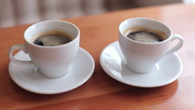 Close-up of two cups of coffee on the table. Close-up of two white coffee cups standing on the table in a cafe stock video