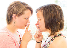 Close up of Two Cute Girls Asking for Silence Royalty Free Stock Images