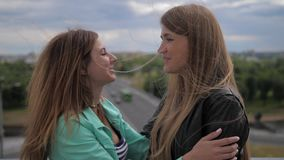 Close-up, two cute and laughing young women say goodbye to each other. Close-up of two cute and laughing young women say goodbye to each other. They embrace stock video