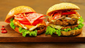 Close up of two delicious hamburgers with beef, bacon, onion, tomato, lettuce and cheese with some ketchup on wooden. Board royalty free stock photography