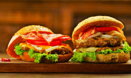 Close up of two delicious hamburgers with beef, bacon, onion, tomato, lettuce and cheese with some ketchup on wooden. Board Stock Photography