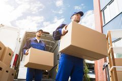 Close-up Of Two Delivery Men Carrying Cardboard Box. Close-up Of Two Young Delivery Men Carrying Cardboard Box In Front Of Truck stock photos