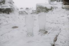 Close up on two empty beer glasses in the snow Royalty Free Stock Image