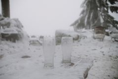 Close up on two empty beer glasses in the snow Royalty Free Stock Photo