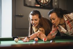 Practice Makes Perfect. Close-up of two female friends playing a game of pool. They are lining up the shot and practicing stock images