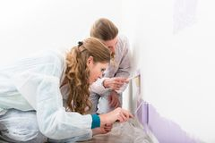 Two female worker giving purple color on the wall. Close-up of two female worker giving purple color on the wall with roller and paint brush stock photography