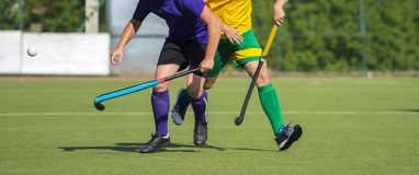 Close up of two field hockey players, challenging eachother for the control and posession of the ball during an intense, competiti. Ve match on professional royalty free stock images