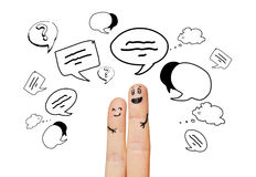 Close up of two fingers with communication clouds. Communication, family, couple, people and body parts concept - close up of two fingers with different facial Royalty Free Stock Image
