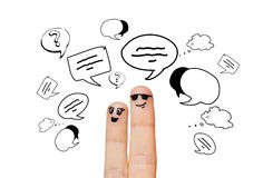 Close up of two fingers with communication clouds. Communication, family, couple, people and body parts concept - close up of two fingers with different facial Stock Images