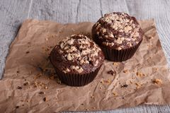 Close-up two chocolate muffins with nuts on a table background. Chocolate cupcakes. Homemade pastry. stock photo