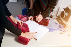 Two young beautiful women working. Close-up, two furrier women discuss how to cut a fur coat from natural fur, on the table lie samples of fur and sketch of a Royalty Free Stock Images