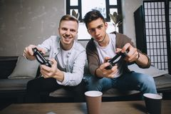 Gamers playing party. Close up of two gamers sitting close one to another on the sofa. They are holding gamepads in their hands and trying to play as best as Stock Photo