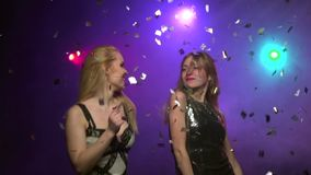 Close-up of two girlfriends dancing in disco style. Slow motion jumping. Close-up of two girlfriends in tight short dresses dancing, jumping and having fun in a stock video footage