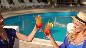Close-up of two girls clink cocktail by the pool. Two young girls clink glasses with a refreshing cocktail with ice on a background of pool, close-up. Slow stock video