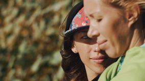 Close up of two girls faces. Windy day outside, bushes leaves on a background. Close up of two girls faces. One of them wearing snapback cap and a hoodie. Windy stock video