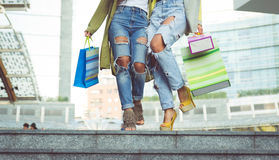 Close up on two girls with shopping bags. Crazy girls making shopping in the city center royalty free stock image