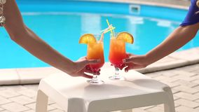 Close-up of female hands take cocktails by pool. Close-up two girls take cocktails on the background of the pool stock footage