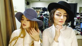 Close-up of two girls to trying on hats. Girls in lilac and black hat stock video