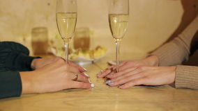 Close-up two glasses champagne and female`s hands. Close-up of two glasses with champagne in the hands of the girls in the cafe stock video