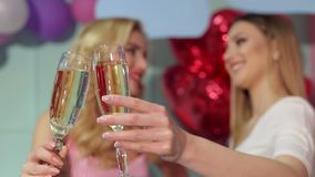 Close-up of two glasses of champagne for two girls. Close-up of two glasses of champagne in the hands of two girls at a party on a bright background stock video
