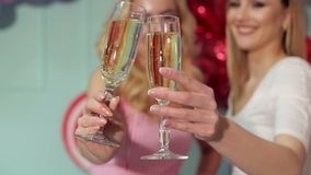 Close-up of two glasses of champagne at the party. Close-up of two glasses of champagne in the hands of two girls at a party on a bright background stock video