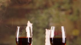 Two glasses of red wine and smoky candles. Close up of two glasses of red wine with smoky candles on background stock footage