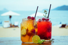 Close up of two glasses with refreshing strawberry cocktail with lime, apple and mint on sea beach background