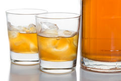 Close up on two glasses of whiskey on the rocks, with a whiskey bottle in white background Royalty Free Stock Photos