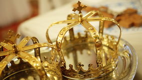 Close up of two gold wedding crowns prepared for ceremony  of marriage in a  church. Close up of two gold wedding crowns prepared for ceremony  of marriage in a stock footage